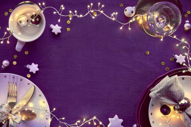 Weihnachtstischaufstellung mit weißem teller und goldenen utensilien und vergoldeten dekorationen. flache lage, draufsicht auf dunkles leinentextil