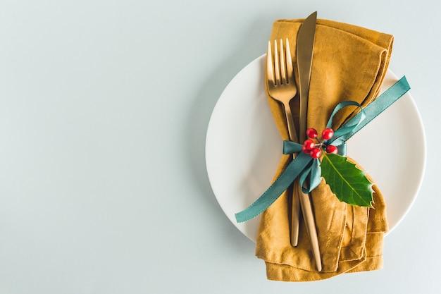 Weihnachtstischbesteck mit serviette auf platte