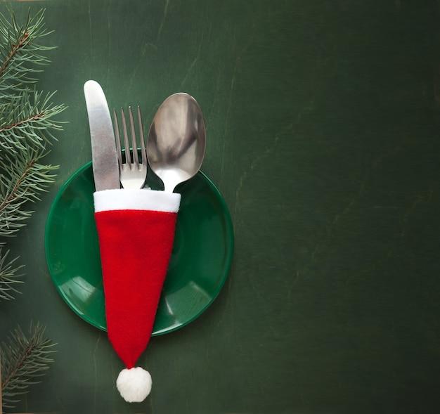 Weihnachtstischdekoration auf grünem hintergrund mit einem tannenzweig als menügestaltungselement
