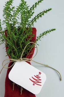 Weihnachtstischdekoration im minimalistischen stil, rote serviette mit gesunden kräutern und tischkarte mit weihnachtsbaum