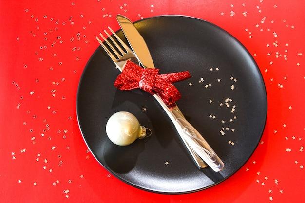 Weihnachtstischdekoration in schwarzer platte mit weißer kugel auf rotem tischweihnachtsessen