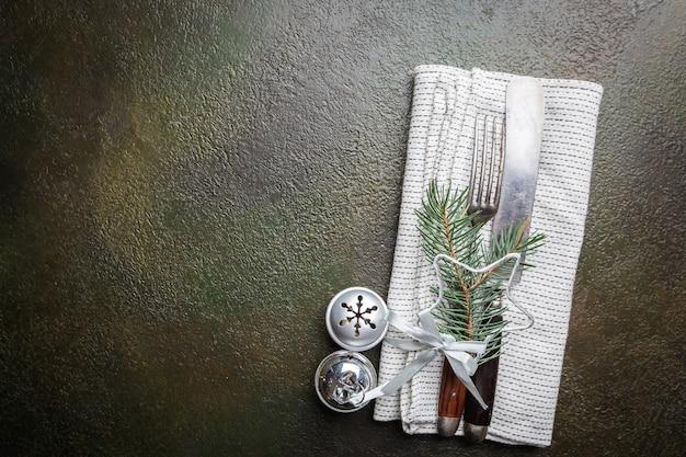 Weihnachtstischgedeck mit weihnachtsbaumasten, messer und gabel über dunklem tisch, draufsicht mit exemplar. weihnachtsferien hintergrund
