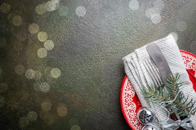 Weihnachtstischgedeck mit weihnachtsbaumasten, teller, messer und gabel über dunklem tisch, draufsicht mit exemplar. weihnachtsferien hintergrund