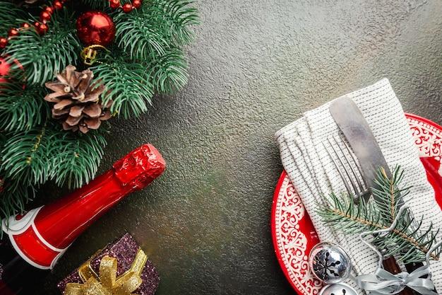 Weihnachtstischgedeck mit weihnachtsbaumzweigen, champagner, teller, messer und gabel über dunklem tisch, draufsicht mit exemplar. weihnachtsferien hintergrund