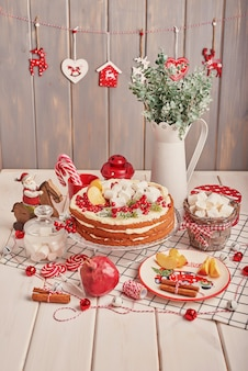 Weihnachtstischschmuck, festlicher fruchtkuchen mit bonbons auf dem tisch