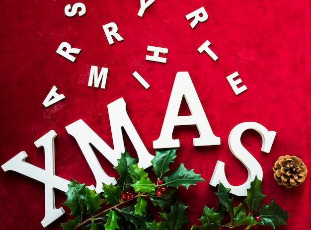 Weihnachtstitel in der nähe von baumstumpf, buchstaben und grünem zweig