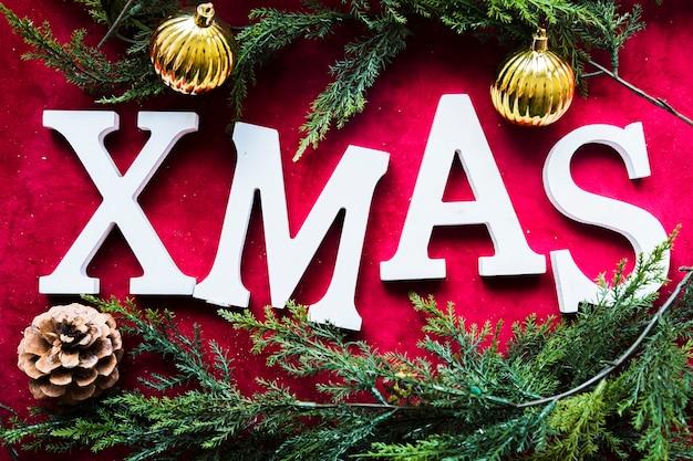 Weihnachtstitel zwischen grünen nadelzweigen und zierkugeln