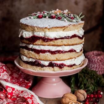 Weihnachtsüberlagerter kuchen mit himbeermarmelade und schlagsahne