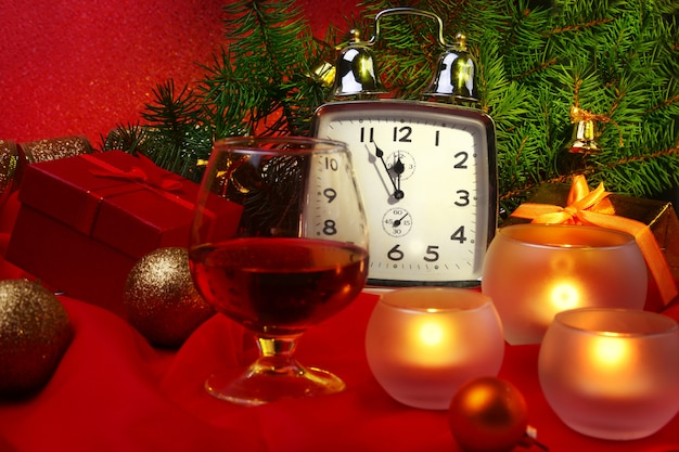 Weihnachtsuhr, glas mit cognac oder whisky und kerzen. neujahrsdekoration mit geschenkboxen, weihnachtskugeln und baum. feier-konzept für neujahr.