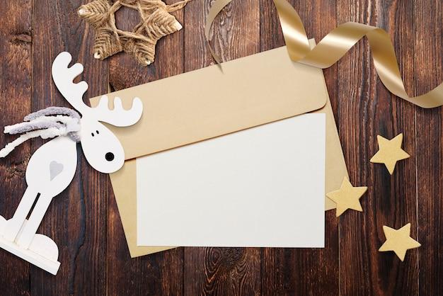 Weihnachtsumschlag mit leerem papier auf braunem holztisch
