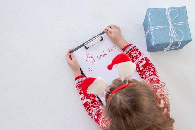 Weihnachtsverkauf. kind hält stift und schrift auf weißer oberfläche. neujahrsverkauf