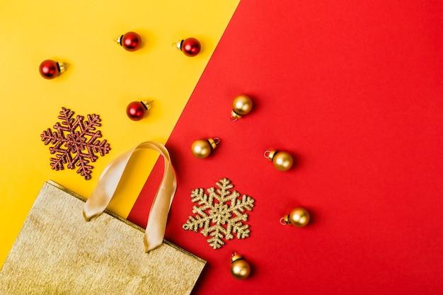 Weihnachtsverkaufskonzept. goldene papiereinkaufstasche, schneeflocken und bälle auf geometrischem gelb-rotem hintergrund.