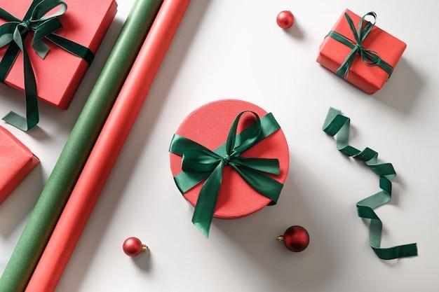 Weihnachtsverpackungsgeschenke mit roter und grüner dekoration auf grau.
