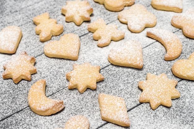 Weihnachtsverschiedene geformte plätzchen mit zuckerpulver auf holztisch