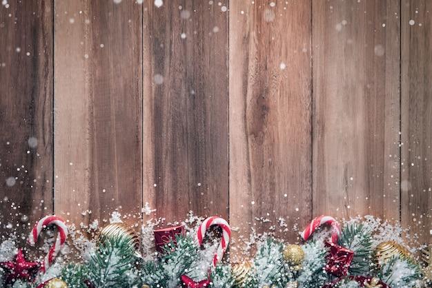 Weihnachtsverzierungen mit schnee auf hölzernem hintergrund
