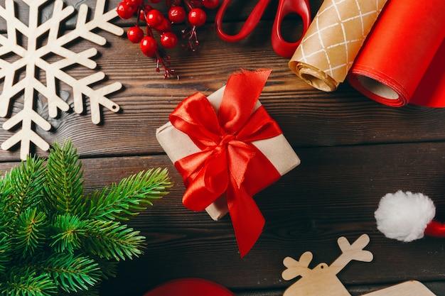 Weihnachtsvorbereitungen. geschenk mit papier und band einwickeln