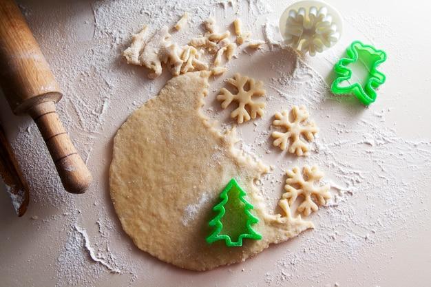 Weihnachtsvorbereitungen: hausgemachte kekse in form eines weihnachtsbaumes und schneeflocken. gerollter teig auf dem tisch und messer, nudelholz. weihnachtsstimmung, backen, familie, hauptkonzept