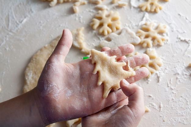 Weihnachtsvorbereitungen: hausgemachte kekse in kinderhandform eines weihnachtsbaumes und schneeflocken. weihnachtsferienstimmung, backen, familie, hauptkonzept