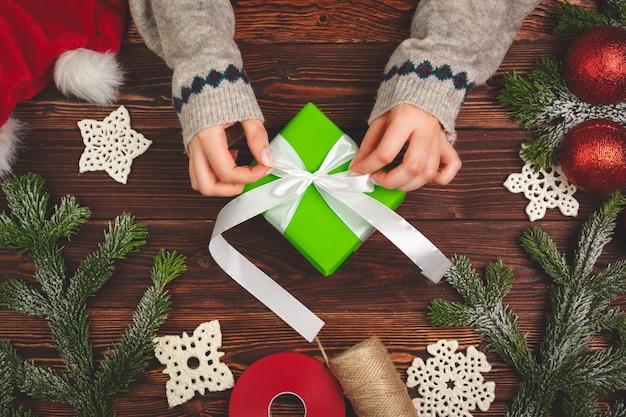 Weihnachtsvorbereitungen konzept. frau, die geschenke nah oben einwickelt
