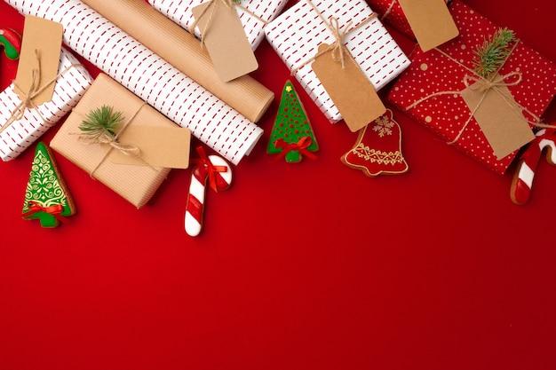 Weihnachtsvorbereitungskonzept mit geschenkpapier, geschenkboxen auf rot