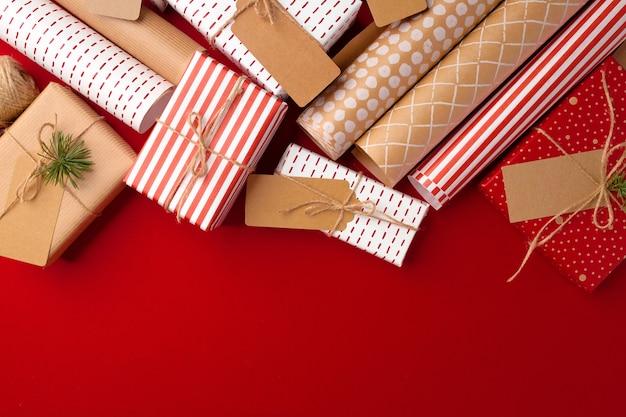Weihnachtsvorbereitungskonzept mit geschenkpapier, geschenkboxen auf rotem hintergrund mit kopienraum
