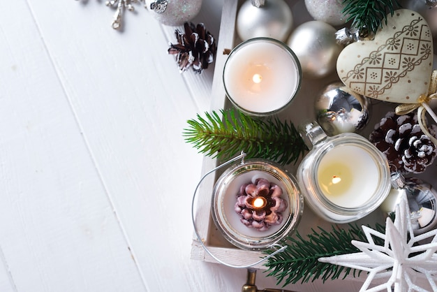 Weihnachtsweihnachtskarte mit glühender kleiner kerze und tannenzapfen