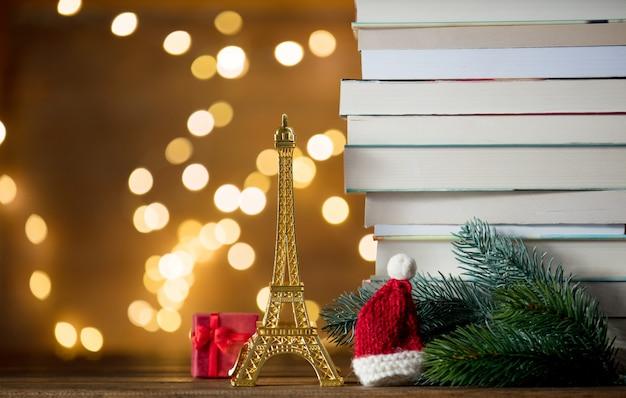 Weihnachtsweihnachtsmann-hut mit eiffelturm und stapel von büchern