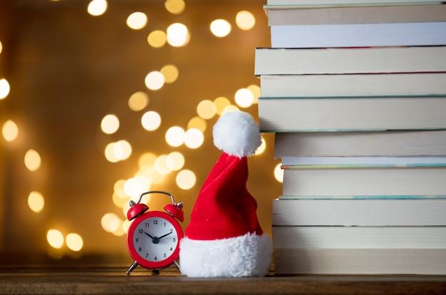 Weihnachtsweihnachtsmann-hut und stapel der bücher