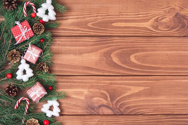 Weihnachtsweinleserahmen. grüne tannenzweige mit süßigkeiten, geschenkboxen, zapfen und weihnachtsspielzeug auf dunklem holzhintergrund. mock-up der retro-feiertagskarte. platz kopieren, flach legen.