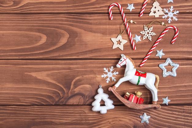 Weihnachtsweinleserahmen. weihnachtsspielzeug, süßigkeiten, bonbons, schneeflocken auf dunklem holzhintergrund. mock-up der retro-feiertagskarte. platz kopieren, flach legen.