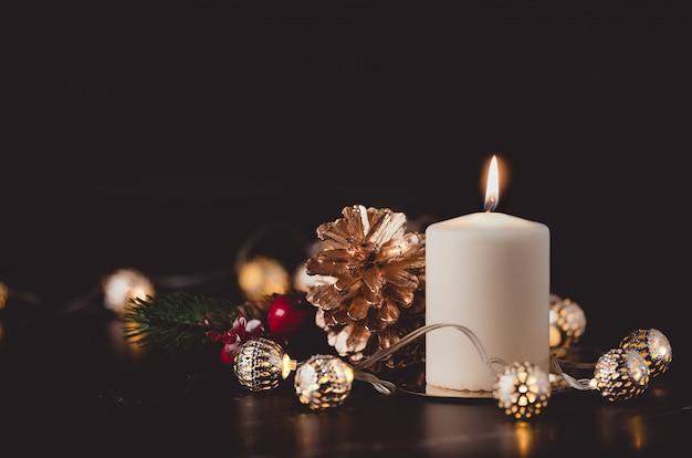 Weihnachtsweiße kerze mit goldenem kiefernkegel, mistelzweig und hellem schnurlicht