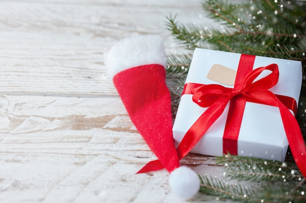 Weihnachtsweißer kasten oder -geschenk mit rotem band für geheime sankt mit sankt-hut auf holztisch.