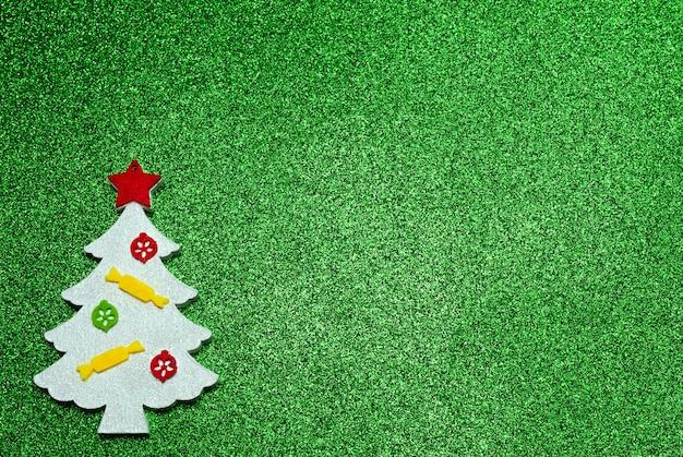 Weihnachtsweißes handgemachtes holzspielzeug in form eines weihnachtsbaumes auf einem glitzernden hintergrund
