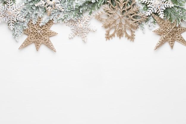 Weihnachtsweißtannenzweige mit goldsterndekorationen.