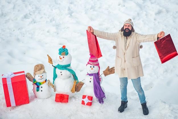 Weihnachtswinter-menschenporträt. weihnachtsvorbereitung - lustiger bärtiger mann mit roter geschenkbox machen