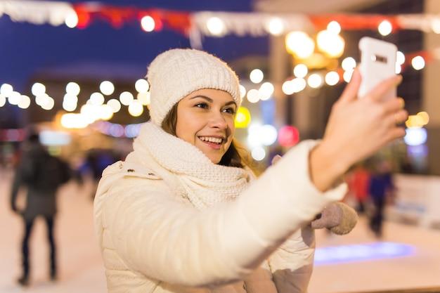 Weihnachtswintertechnologie und -freizeitkonzept glückliche junge frau, die foto mit smartphone an macht