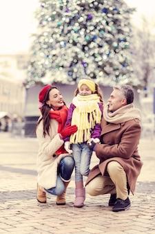 Weihnachtswochenenden. erfreute langhaarige frau, die ein lächeln auf ihrem gesicht behält, während sie ihr kind ansieht