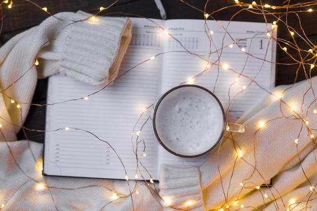 Weihnachtswohnung komposition mit warmem pullover, weihnachtsbeleuchtung, notizblock und kaffee.