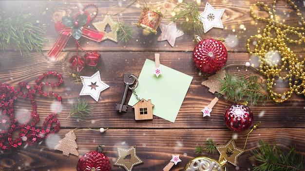 Weihnachtswohnung lag auf einem hölzernen hintergrund mit schlüsseln zu einem neuen haus in der mitte