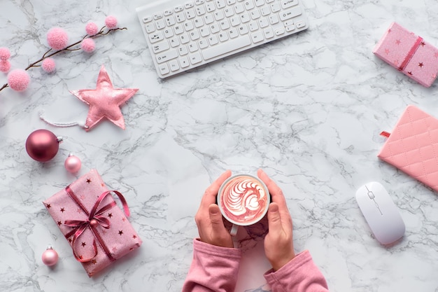 Weihnachtswohnung lag auf marmortisch. hände, die sich von einer warmen tasse cafe latte oder heißer schokolade mit herzform aufwärmen. winterdekorationen: tannenzweige, sterne und rosa schmuckstücke, kopierraum