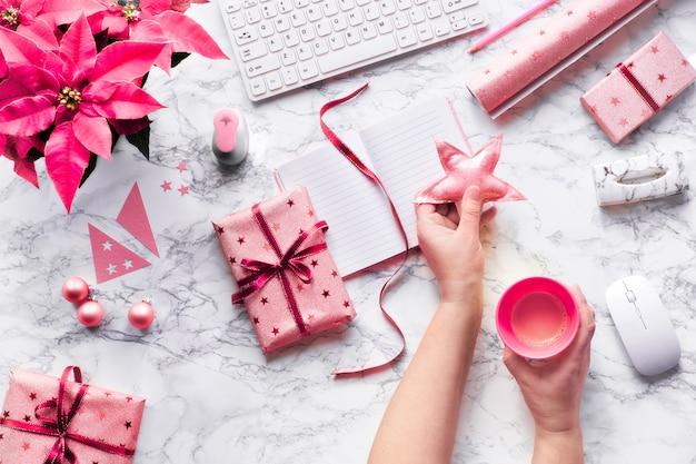 Weihnachtswohnung lag auf marmortisch. hände halten stern und tasse kaffee. winterdekorationen - leuchtend rosa weihnachtsstern, tannenzweige, weiche sterne und schmuckstücke.
