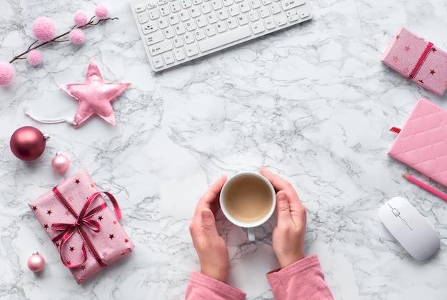 Weihnachtswohnung lag auf marmortisch. hände wärmen sich von heißer tasse kaffee auf. tannenzweige, weiche sterne und rosa schmuckstücke, kopierraum
