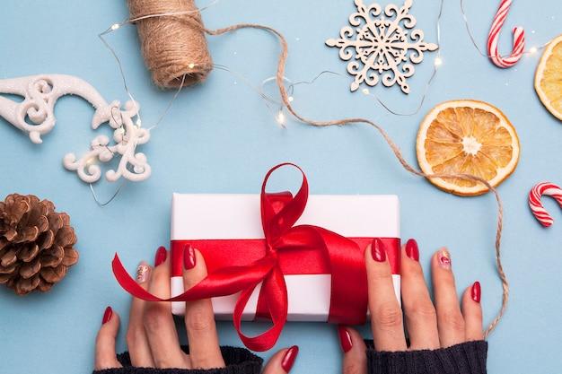 Weihnachtswohnung lag mit einem geschenk in frauenhänden. winterferienkonzept