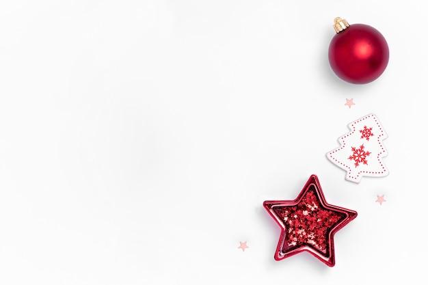Weihnachtswohnung lag mit roten kugeln, weißen sternen und weihnachtsbaum auf weißem papier