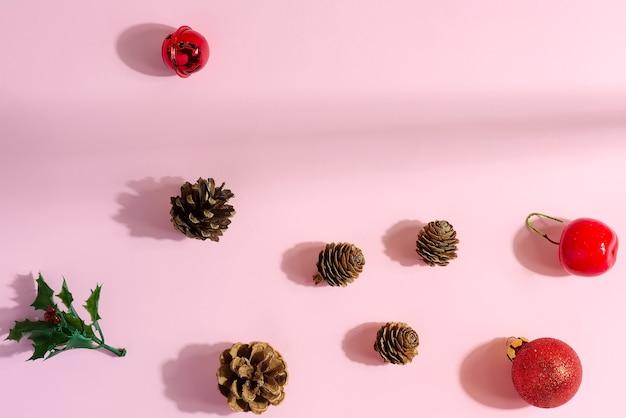 Weihnachtswohnung lag mit unterschiedlicher dekoration: tannenzapfen und festliche kugeln auf pastellrosa.