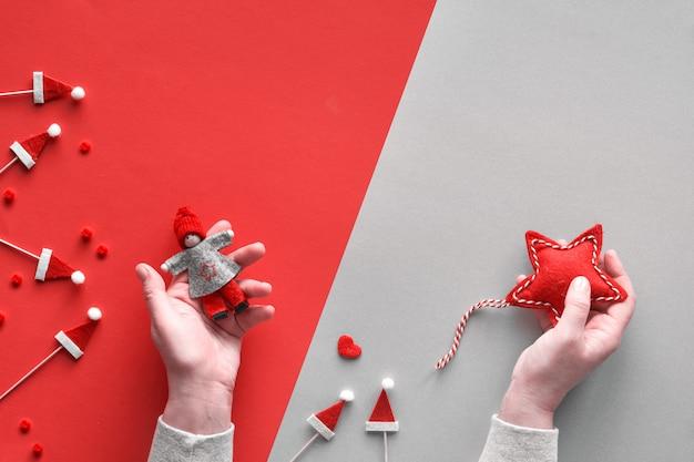 Weihnachtswohnung lag mit weiblichen händen, die textilstern und dekorative puppe auf diagonalem papierhintergrund in grau und rot mit roten weihnachtsmützen halten. flache lage, draufsicht von oben mit kopierraum.