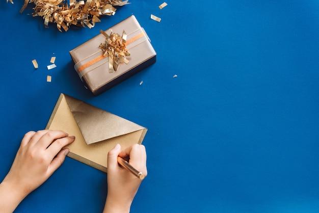 Weihnachtswünsche mit goldbox und kranz schreiben