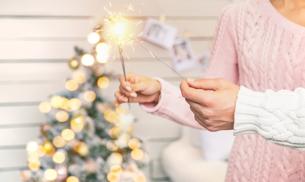 Weihnachtswunderkerzen in den händen eines mannes und einer frau. urlaub. selektiver fokus. personen.