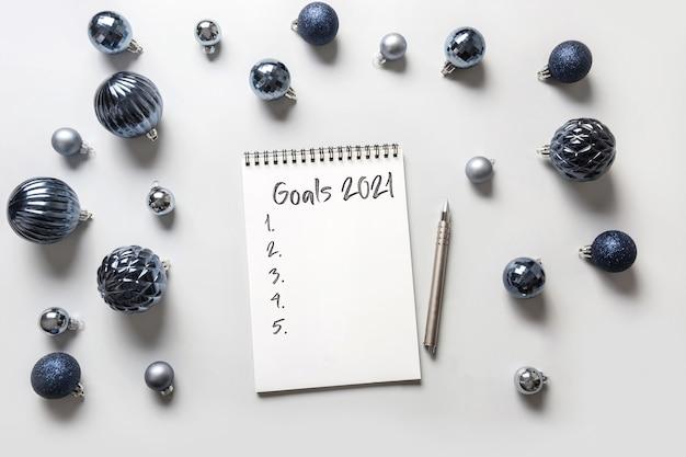 Weihnachtswunschliste, checkliste, listenaktivität für 2021 neujahr mit blauer dekoration auf grau.
