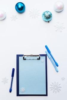 Weihnachtswunschliste. leeres blatt papier, weihnachtskugeln und schneeflocken auf einem weißen